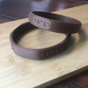 two cork based plastic bangles with the word brave modeled in braille into the face, one circular, one octagonal