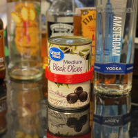 can of black olives wearing a red CanDo label on a shiny bar next to bottled spirits