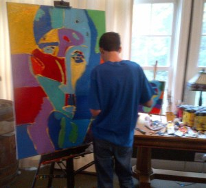 """Artist Jimmy Reagan working on his painting """"Man of the World"""""""