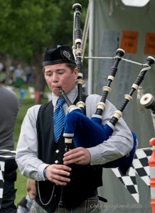 A young member of the North Colorado Caledonia Pipe Band plays a bagpipe, wearing a custom made tie, a vest, and a hat.