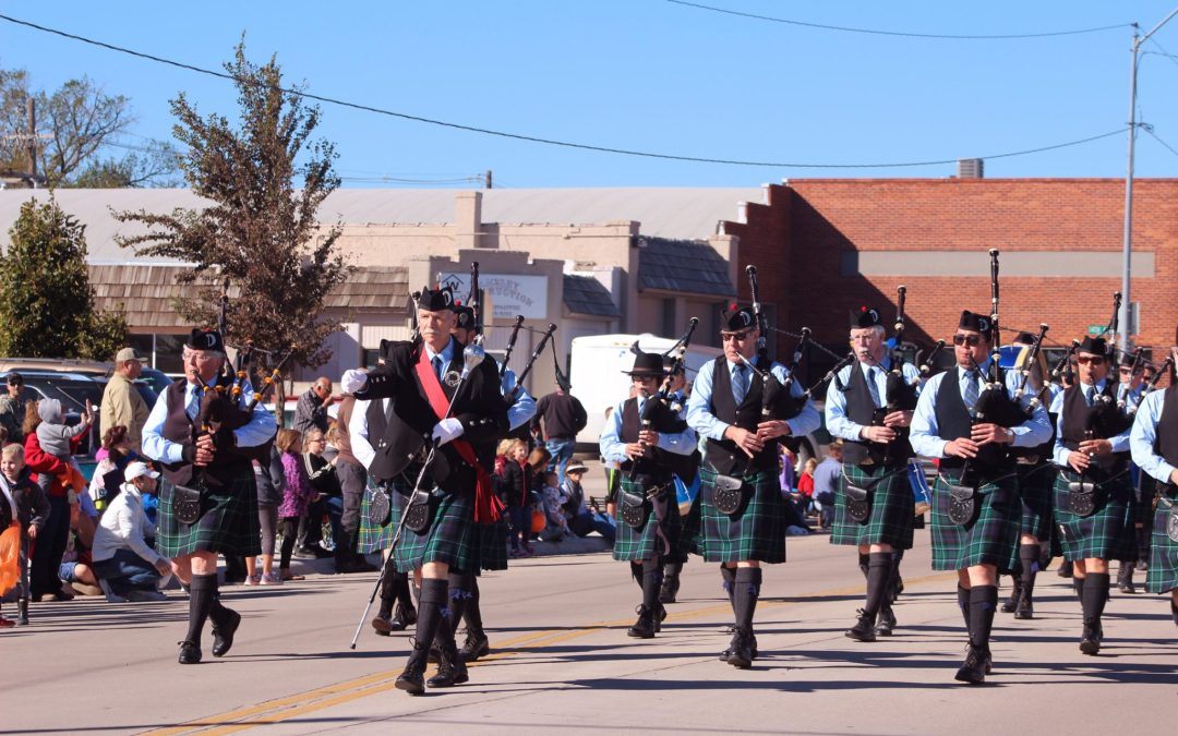Pipe Band members marching down the street with bagpipes and kilts