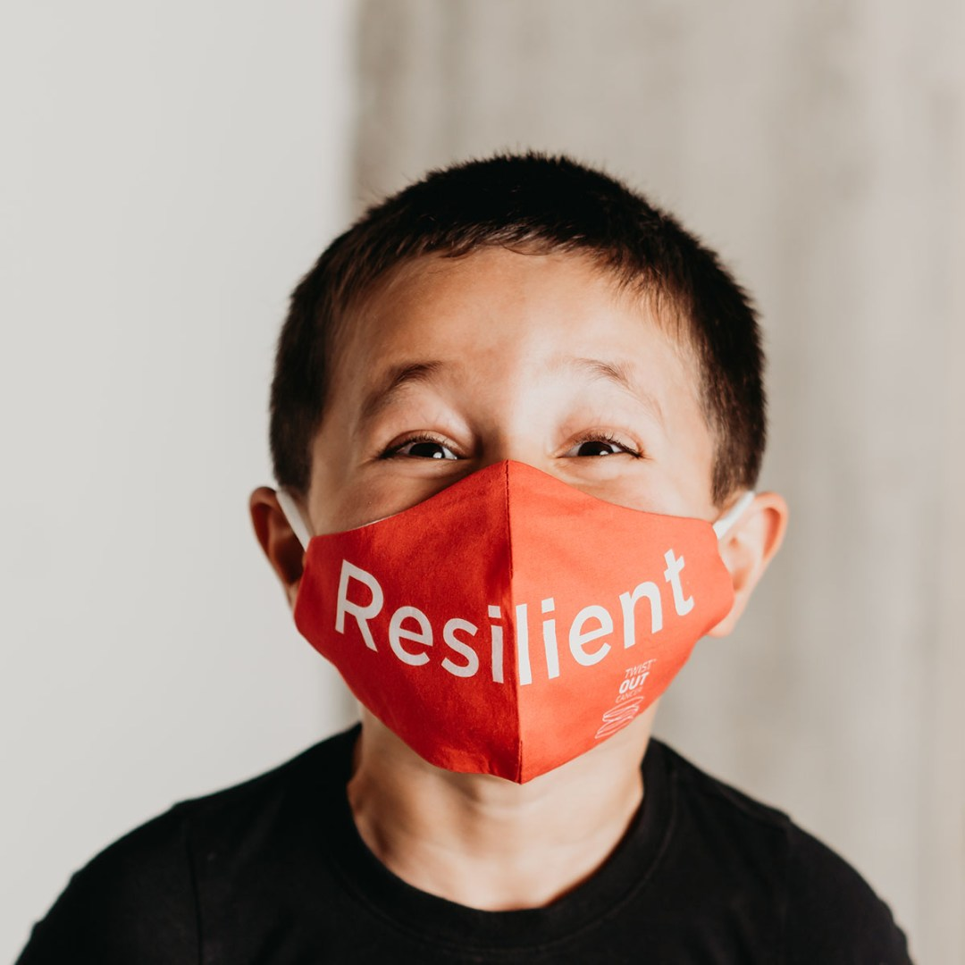 child wearing a kid's size custom orange face mask with reslient font
