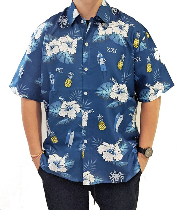 model wearing blue men's Hawaiian shirt with pineapples and floral print