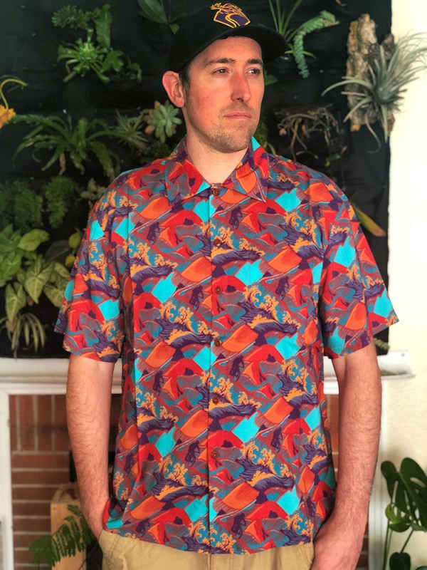 Man in colorful Hawaiian shirt with orange and blue design, standing in front of a wall full of plants
