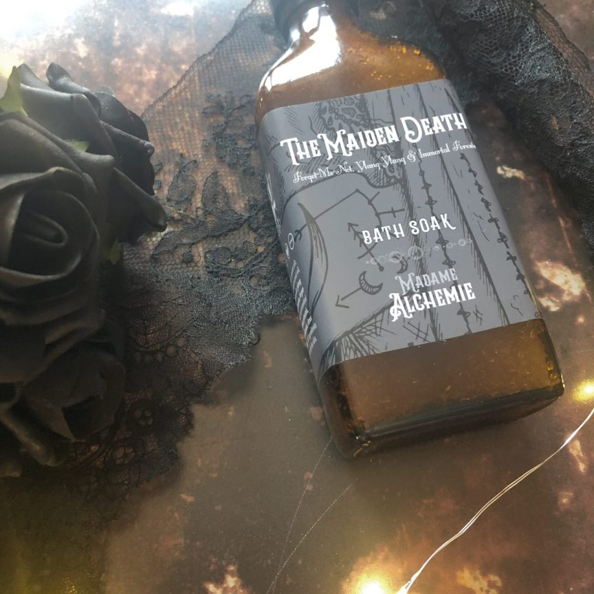 a bottle of the maiden death bath soak by madame alchemie pictured against a copper background with fairy lights and black roses