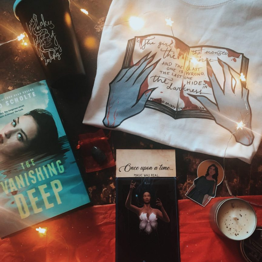 an unboxing of march 'everything has a price' moonlight crate box featuring a tshirt, book, thermos, candle, crystal, magnet and tarot card.