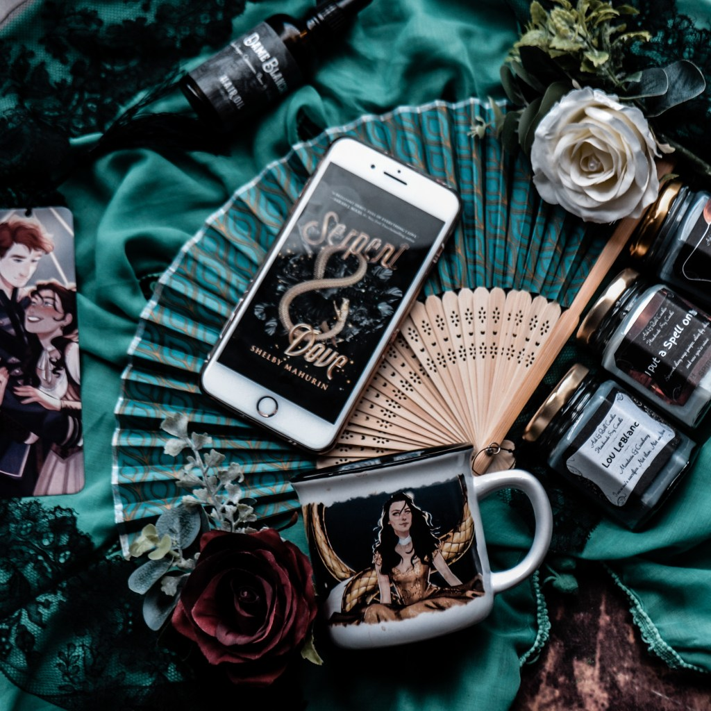 Image shows a range of Serpent & Dove book themed merchandise. In the top corner is a hair oil called Dame Blanche by Madame Alchemie, below on the left is a metalmark Bookmark which was from the Illumicrate June bookbox, in the middle is an iPhone 8+ with the Serpent & Dove ebook cover, below is a mug with Lou from the book pictured. On the right are three witchy inspired candles by Ash and Quill candles; Lou LeBlanc candle, I Put a Spell on You candle and Resting Witch Face candle.