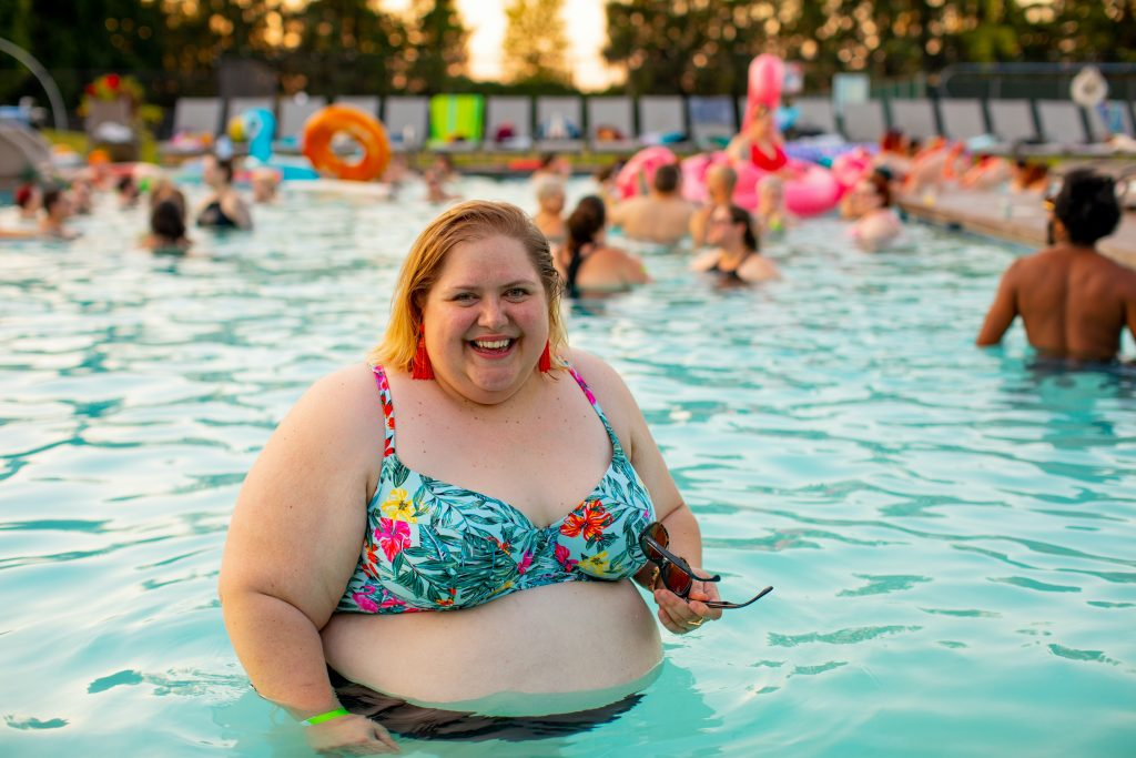 a bigger female body smiling in a swimming pool having fun