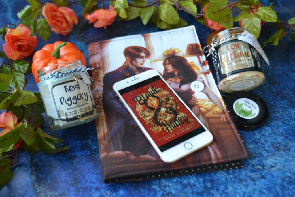 blood and honey kindle book cover on iphone. Also visible is a booksleeve dust jacket with Lou and Reid (main characters from Blood & Honey) character art and candles inspired by the series.