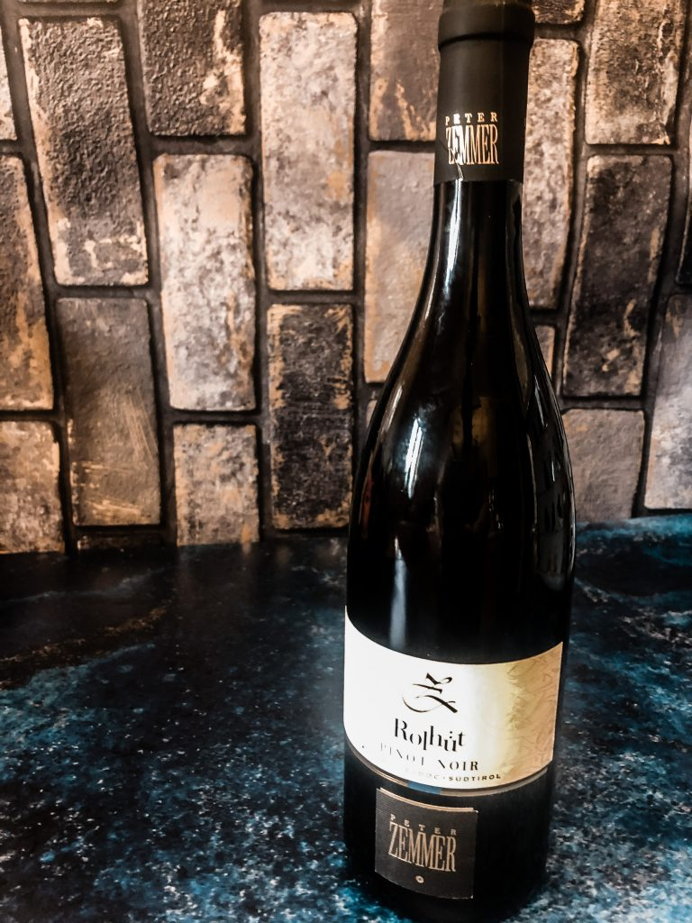 a bottle of Pinot Noir Rolhüt 2018 from Independent Wine on a blue surface with a grey brick background