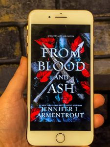 hand holding an iphone 8 plus with the book cover of from blood and ash by jennifer l armentrout