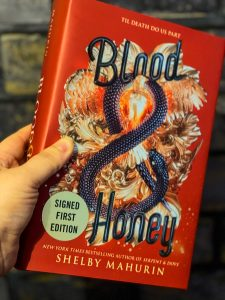 hand holding a copy of blood & honey by shelby mahurin against a grey brick background