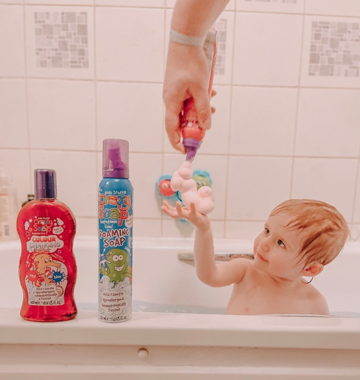 A toddler in the bath with his hand up. An adult hand is holding a bottle of foaming soap and squeezing it into the toddlers hand. There are some Kids Stuff Crazy Bathtime range products in the foreground.