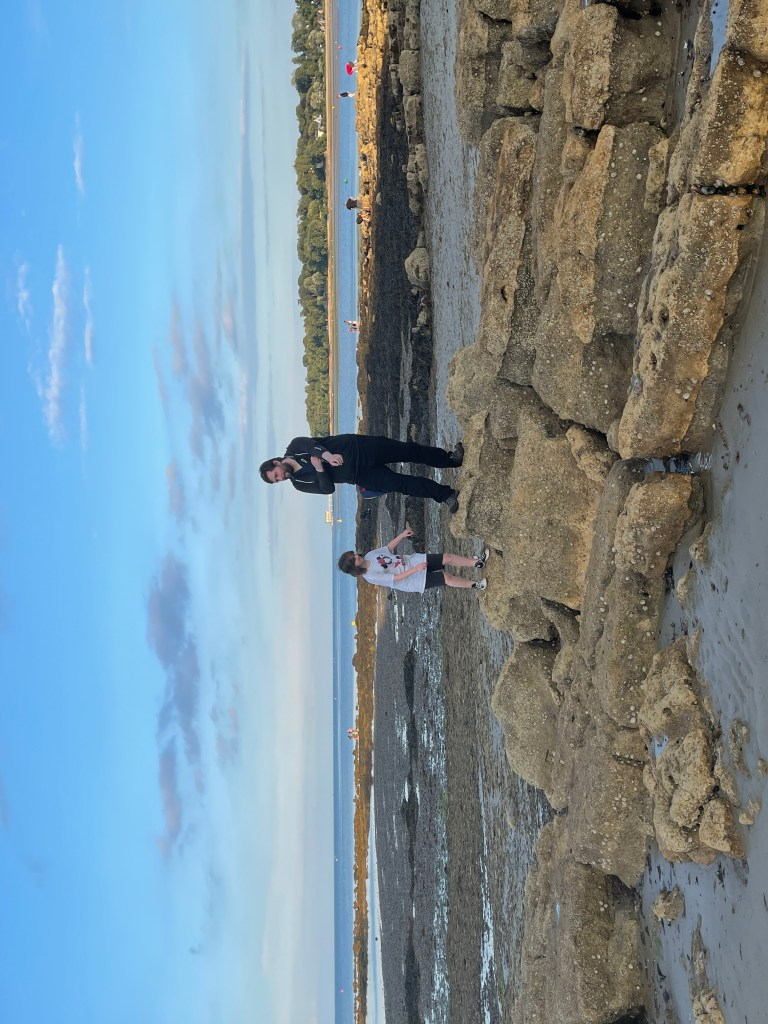 adam and evie looking at rock pools on the beach at nodes point holiday park