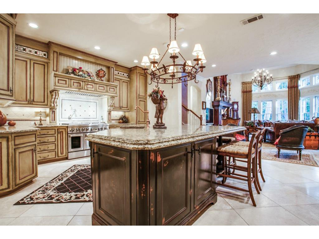 Custom gourmet kitchen features hand painted cabinetry, oversize