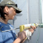 Woman using a caulking gun to set windows