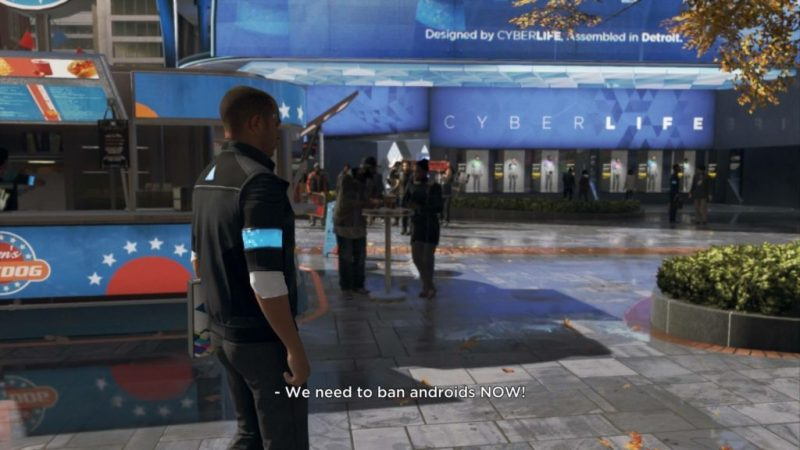 Player controlled character standing in middle of protests in busy downtown area.