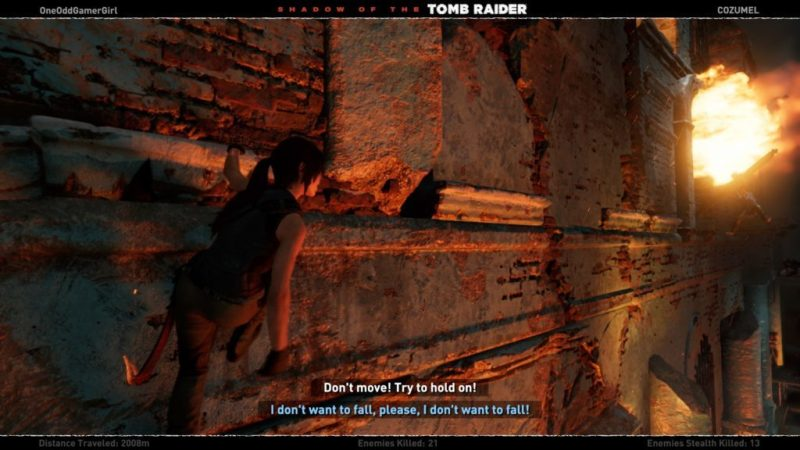 Lara scaling a wall, image showing two different subtitle colors for two speakers.
