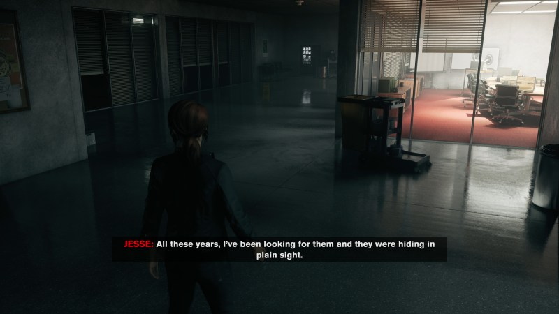 Jesse walking in a dark office area, image displays large subtitles.
