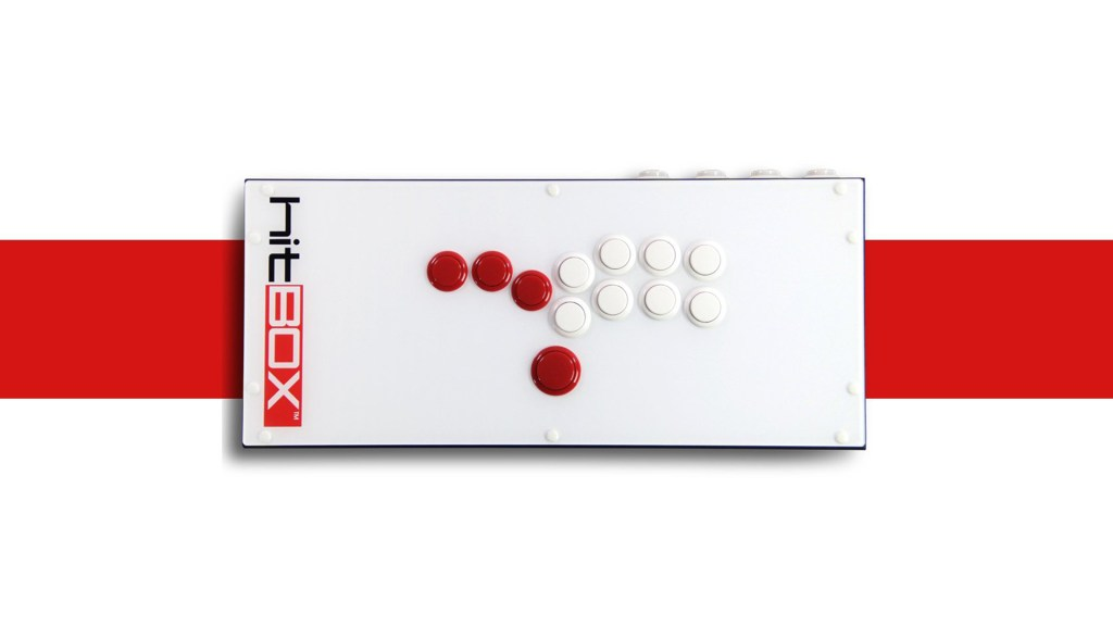 The Hitbox seen from above. Three red buttons are present on the left side, with the middle button positioned slightly above the other two, with a larger red button positioned at the bottom of the device. Two rows of four white buttons are present on the right side of the device, with a slight curve in each row so as to be comfortably reached by specific digits when resting a hand on top of the controller.