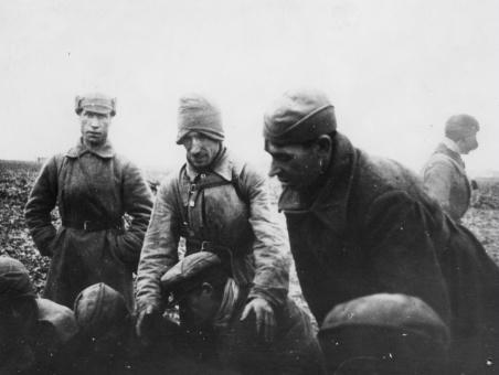 """Część jeńców siedzi na ziemi, czterech ubranych w zimowe szynele, względnie pochyla się. Pierwszy stojący z lewej ma na głowie tzw. """"budionnówkę""""(""""szłom""""), drugi naciągniętą na uszy furażerkę, czwarty czapkę """"uszankę"""" z opuszczonymi nausznikami."""
