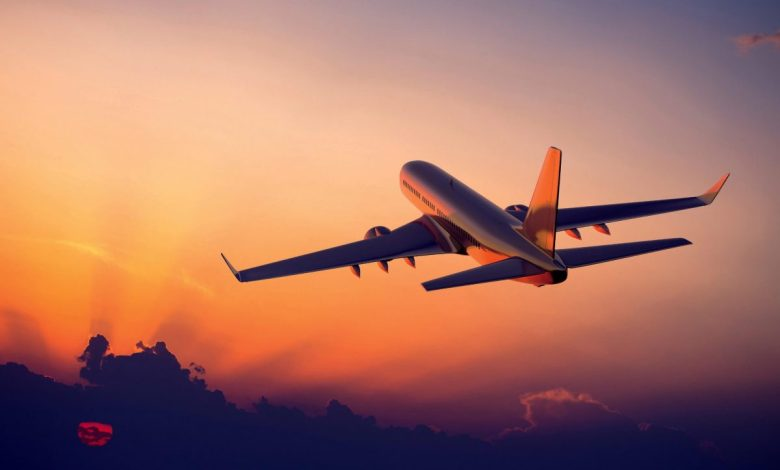 avion planant dans les airs ciel orangé