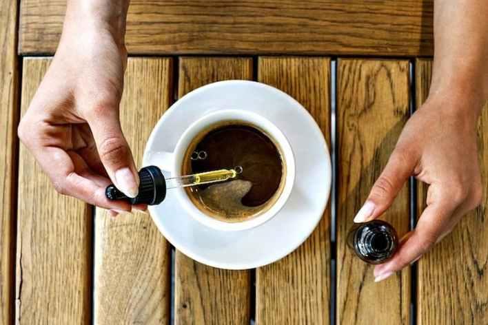 mains de femme qui versent de l'huile de cbd dans une tasse de café,