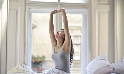 Woman with long black hair sits up and stretches in a white bed in front of a window
