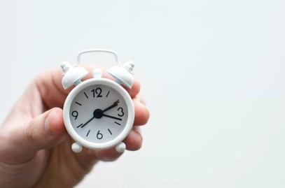 A hand holding a mini white clock which is showing the time as 2:20pm