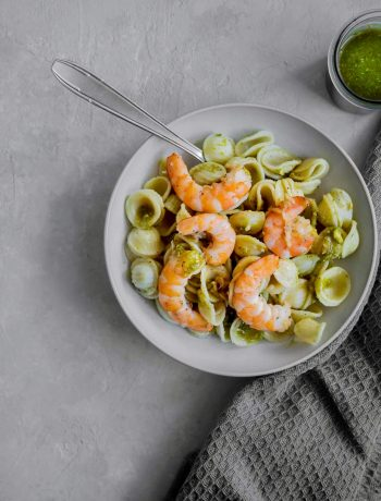 Pot de pesto et assiettes de pâtes aux crevettes