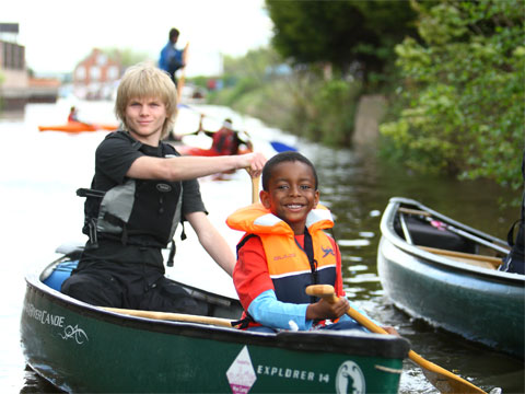 A young man and a boy having fun paddling an open canoe