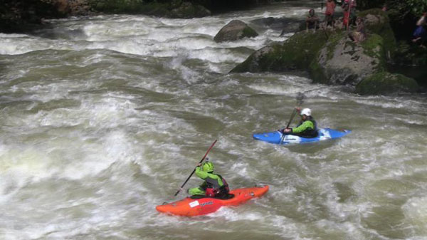 Two kayakers on rapid