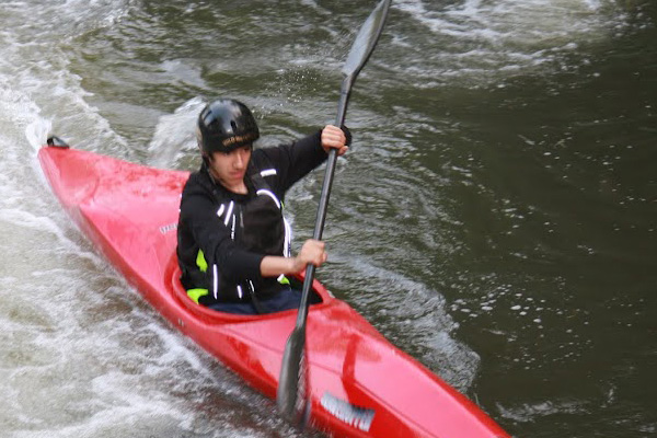Paddler racing a kayak down river