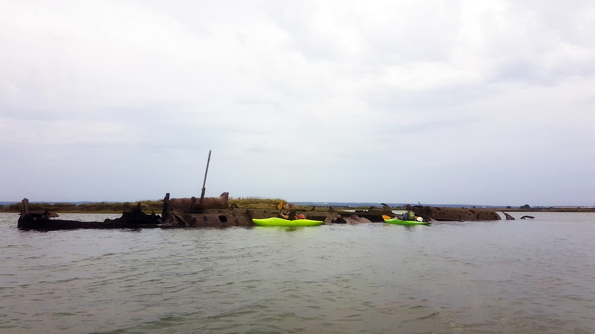 Kayakers alongside the wreck of German U-boat UB122, a submarine found in the River Medway estuary.