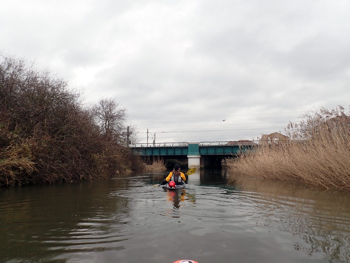 Kayaker on River Roding approaching rail bridge