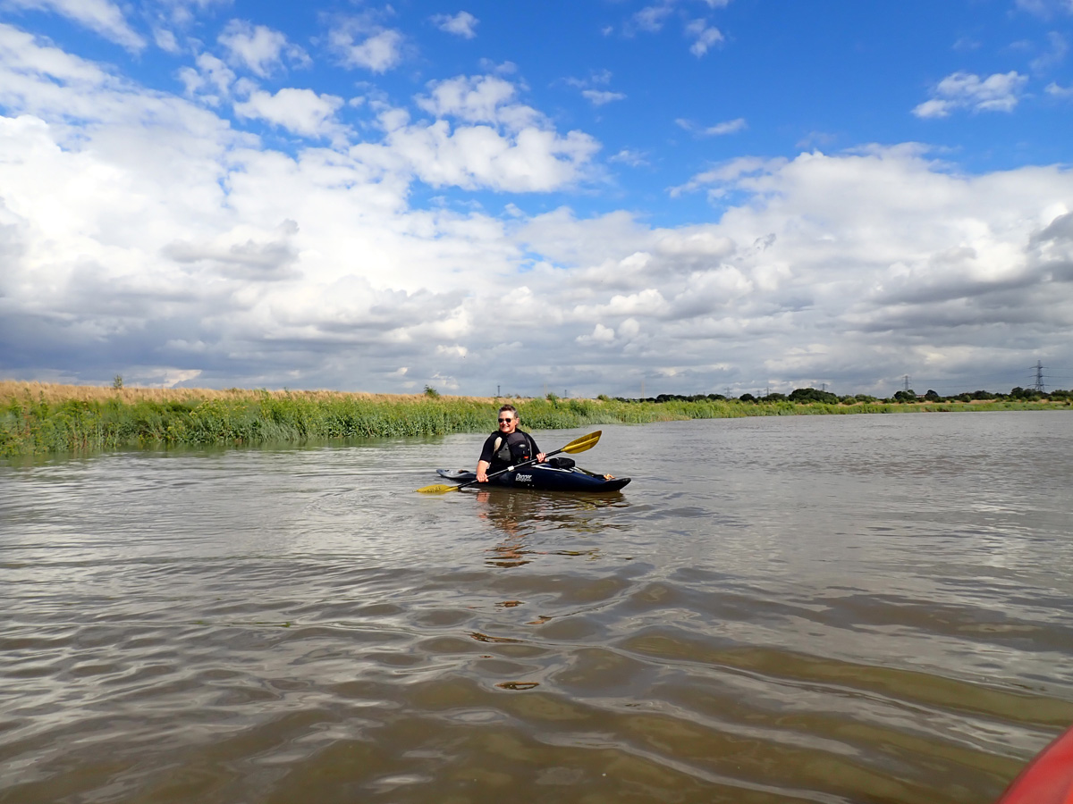A kayaker on the River Darent, with saltmarsh in the background, under a big, blue sky.