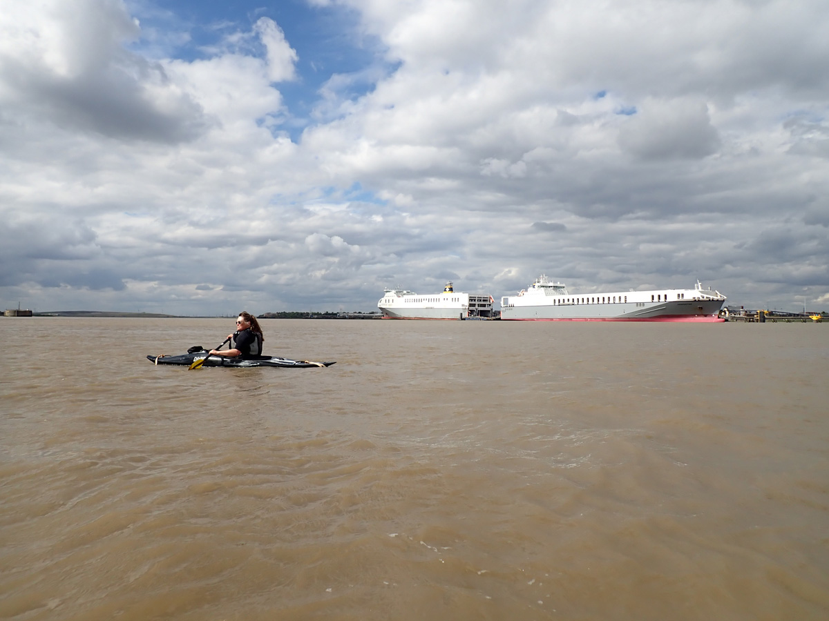Kayaker on the Thames with Purfleet Terminal in the distance