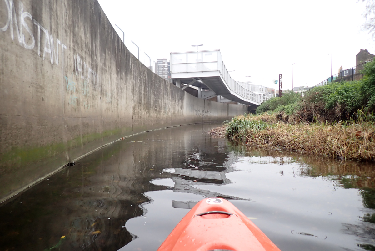 Looking upstream from a kayak on a narrow river. On the left is a concrete river wall. On the right the riverbank is more natural, sloping with plants. Ahead, Elverson Road Docklands Light Railway Station crosses the river.