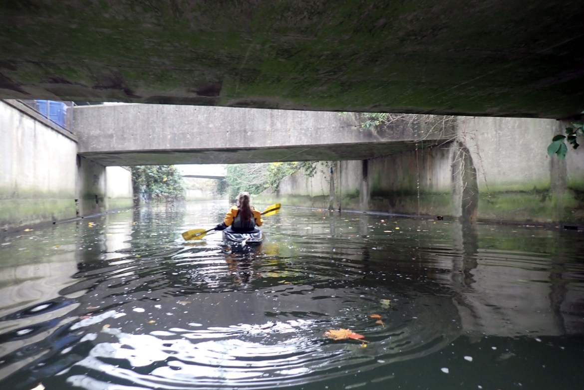 Kayaker on a river flowing between concrete walls and below a series of concrete bridges.
