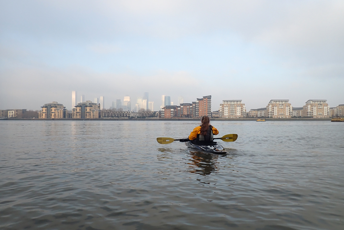 A kayaker on the Thames, looking across the river to the Isle of Dogs and the silvery towers of Docklands.