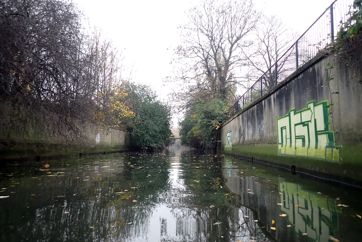 A calm river flowing between tall, graffitied concrete walls, with trees above the walls.