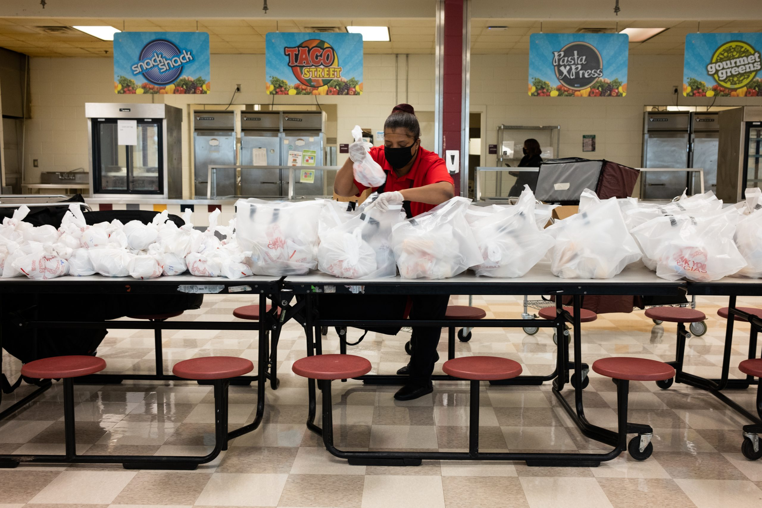 A woman packs dozens of lunches for APS students