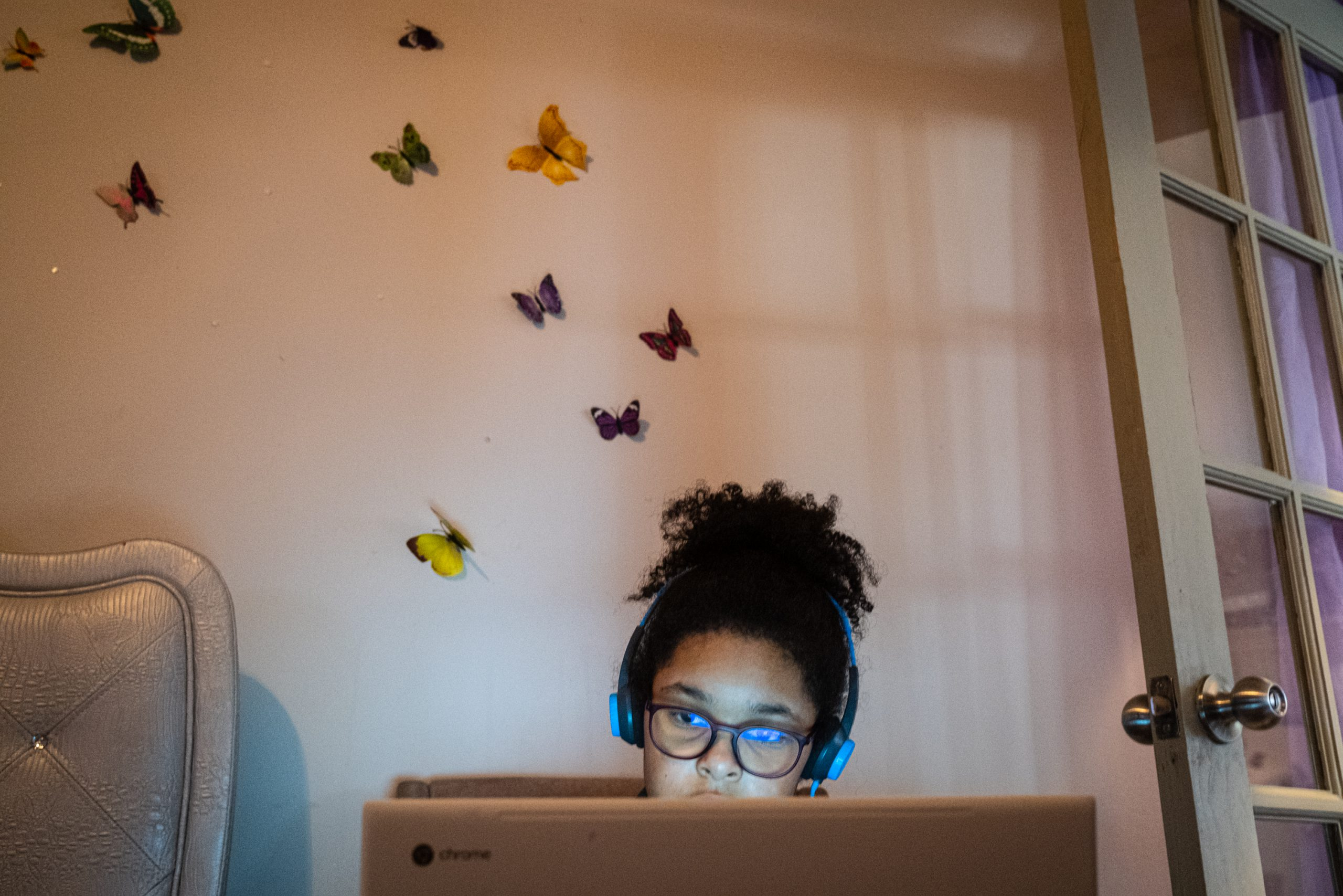 A girl looks at her computer in a room with butterfly stickers on the wall