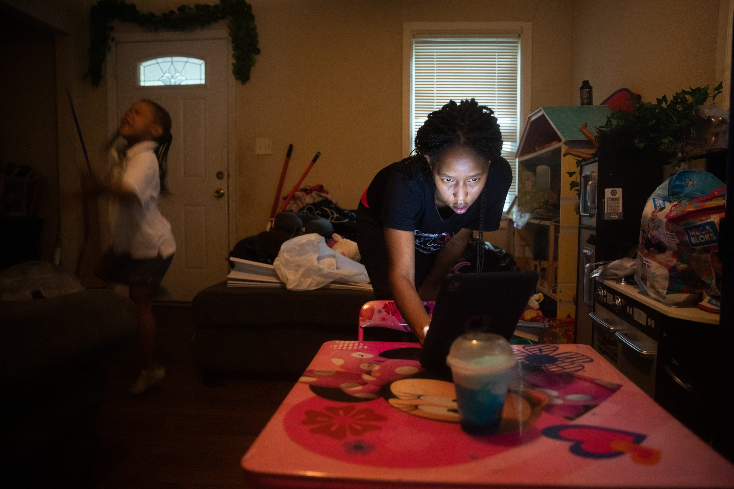 Mom setups up laptop on child's Minnie Mouse desk