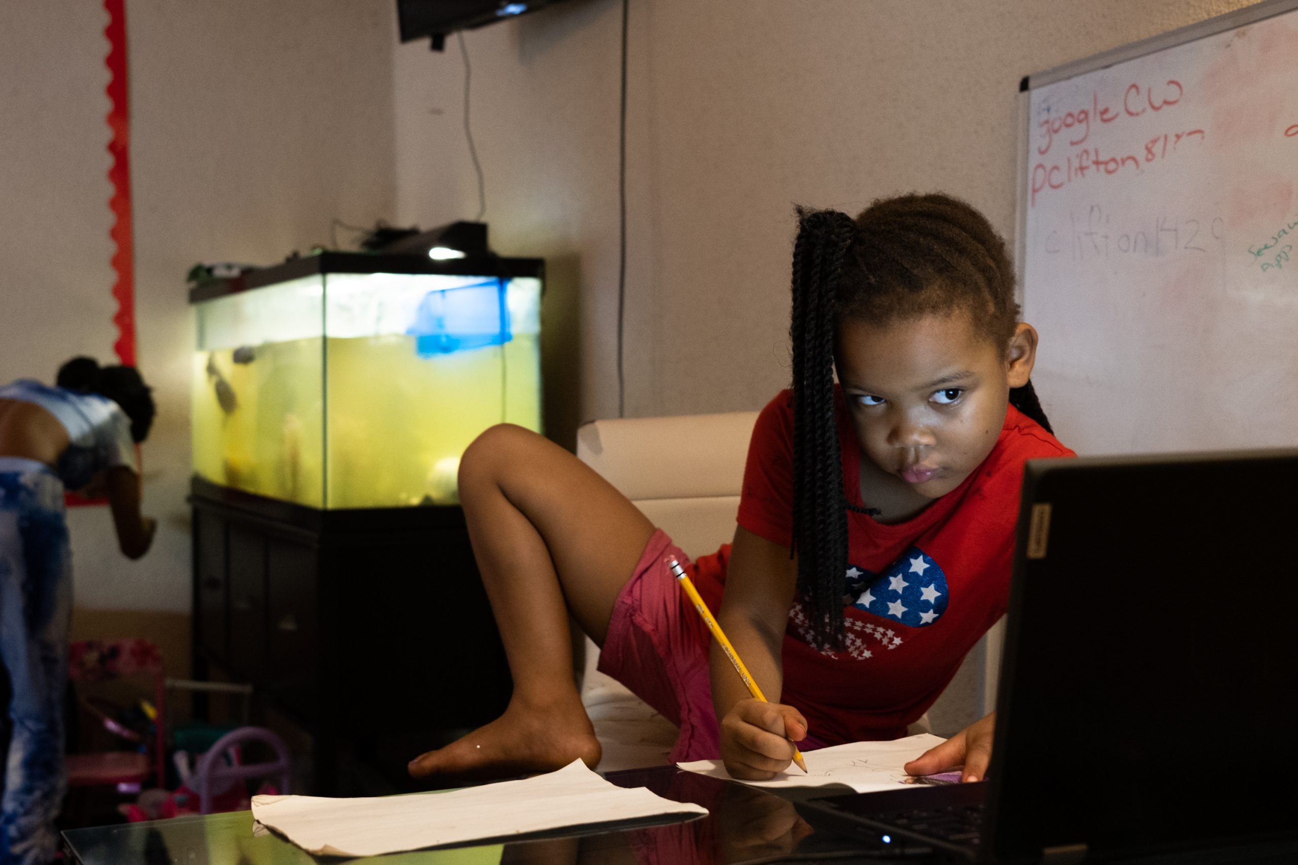 Young girl works on homework with leg on desk