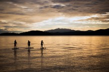 Stand-up paddle boarders three