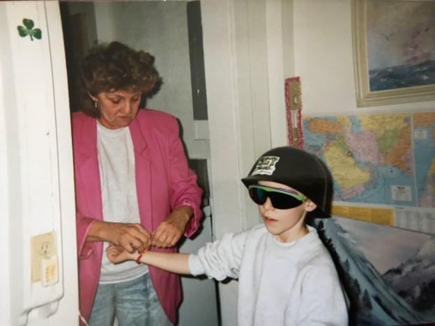 My grandmother putting a bracelet on me while I'm wearing a badass Sgt. Slaughter helmet and sick sunglasses.
