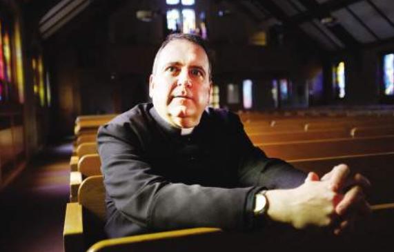 Father Gary Belliveau sitting in a church pew.