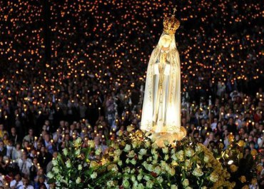 Statue of our Lady of Fatima with a crowd during a candlelight vigil.