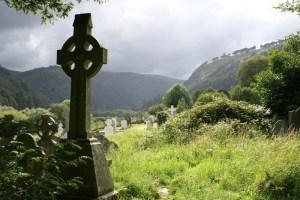 celtic cross tombstone in a graveyard in Ireland